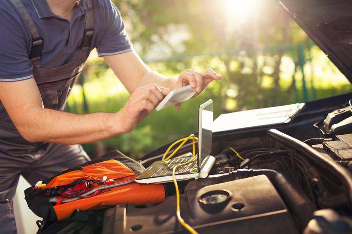 Professional car mechanic using smartphone app